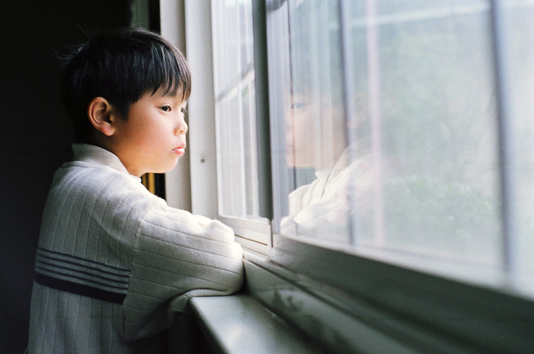 boy watching out a window