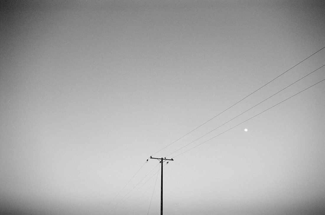 telephone pole with moon in the sky
