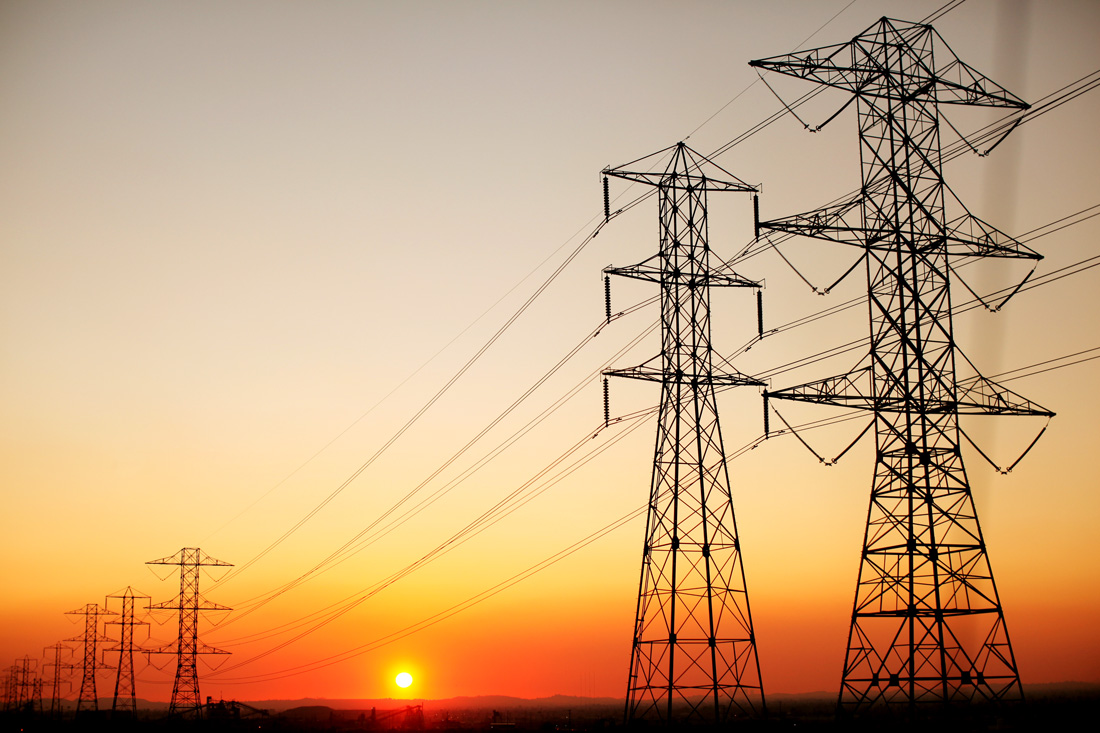 Sun setting behind electric towers