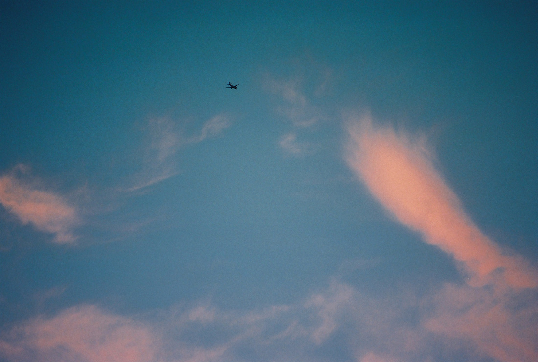 plane flying in blue sky with wisps of clouds